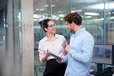 Smiling male and female entrepreneurs discussing at office - p300m2265168 by Florian Küttler