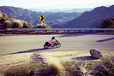 Man wearing pyjamas riding motorcycle, Malibu Canyon, California, USA - p924m1422758 by Raphye Alexius