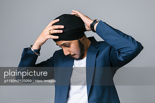 Young Indian businessman adjusting turban - p1192m2123269 by Hero Images