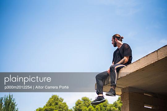 Tattooed man sittin on roof top - p300m2012254 von Aitor Carrera Porté