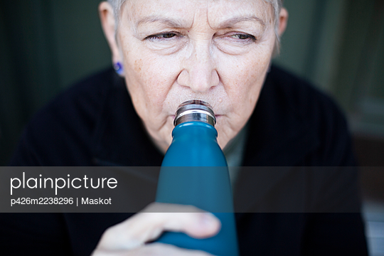 Senior woman drinking water outside house - p426m2238296 by Maskot