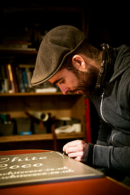 A sign writer working with a loaded brush painting a line freehand on the edge of a sign.  - p1100m1158325 by Mint Images