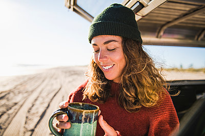 Young woman enjoying cup of coffee in the morning beach car camping - p1166m2285564 by Cavan Images