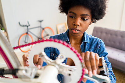 Afro hairstyle woman repairing bicycle chain at home - p300m2276167 by Giorgio Fochesato