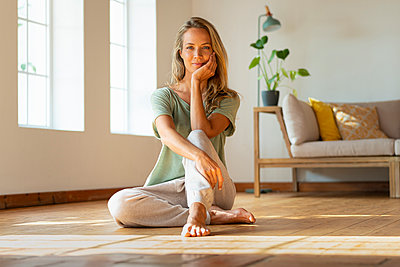 Beautiful woman with hand on chin sitting on floor in living room - p300m2277458 by Steve Brookland