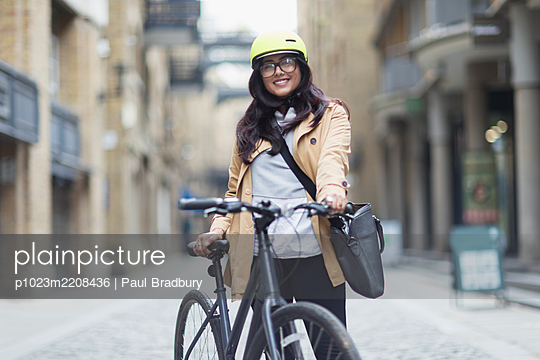 Portrait smiling woman in helmet with bicycle on city street - p1023m2208436 by Paul Bradbury