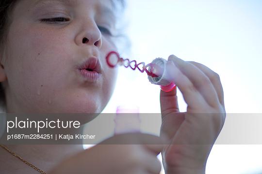 Little girl blowing soap bubbles - p1687m2284251 by Katja Kircher