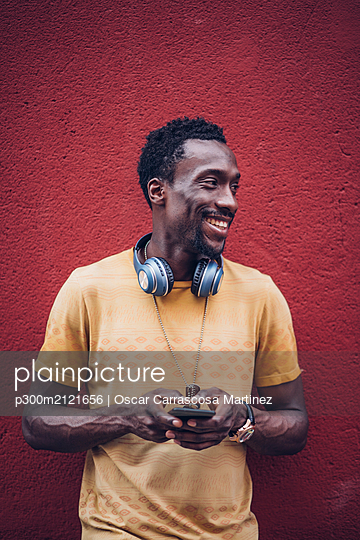 Portrait of smiling man with headphones and smartphone - p300m2121656 by Oscar Carrascosa Martinez
