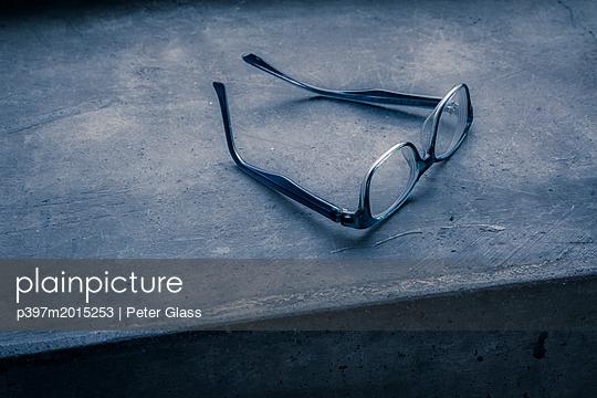 Brille auf einem Fensterbrett aus Beton - p397m2015253 von Peter Glass
