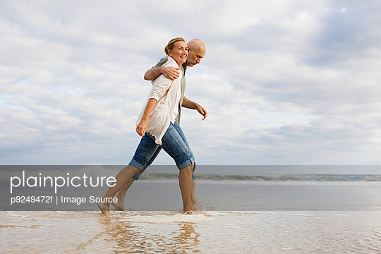 Couple walking in the sea - p9249472f by Image Source