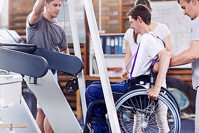 Physical therapists helping man in wheelchair onto treadmill - p1023m1121425f by Trevor Adeline
