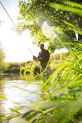 Man fly fishing at sunny river - p1023m2262067 by Martin Barraud