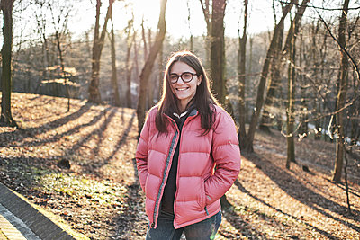 Happy young girl in glasses wearing a pink jacket and jeans - p1166m2177282 by Cavan Images