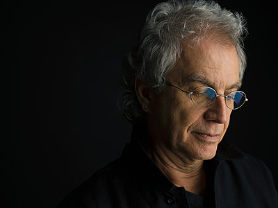 Portrait pensive, serious senior man with gray hair and eyeglasses looking down against black background - p1192m1403638 by Hero Images