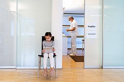 Mädchen mit Tablet PC im Wartezimmer, COVID-19  - p1625m2254570 von Dr. med.
