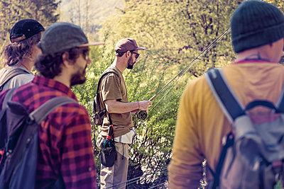 Slovenia, four men preparing for fly fishing in Soca river - p300m1499445 by Matthias Buchholz