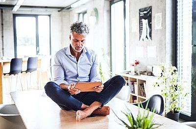 Mature businessman sitting barefoot on desk in office using tablet - p300m1568065 von HalfPoint