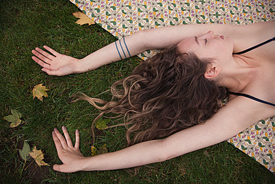 Woman laying on blanket in grass - p555m1409416 by Shestock