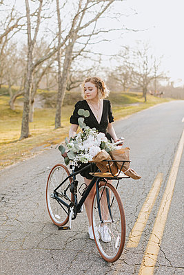 Young woman standing by bicycle with bunch of flowers on rural road,  Menemsha, Martha's Vineyard, Massachusetts, USA - p924m2058139 by Lena Mirisola