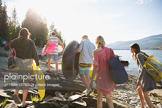 Young friends carrying pool rafts at sunny lakeside - p1192m1078312f by Hero Images