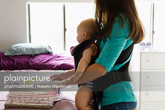 Mid adult woman doing chores with baby daughter in baby sling - p1427m2283200 by Roberto Westbrook