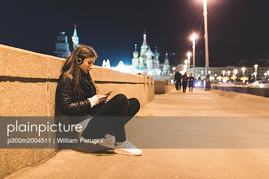 Russia, Moscow, beautiful woman listening music in the city at night - p300m2004511 von William Perugini