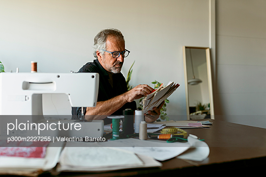 Mature tailor looking at fabric swatch papers while sitting at table in studio - p300m2227255 by Valentina Barreto
