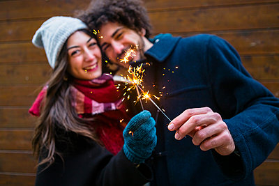 Happy young couple in winterwear holding sparklers in front of wooden wall - p300m2083652 von Giorgio Magini