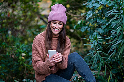 Mid adult woman smiling while using mobile phone in garden - p300m2264567 by Annika List