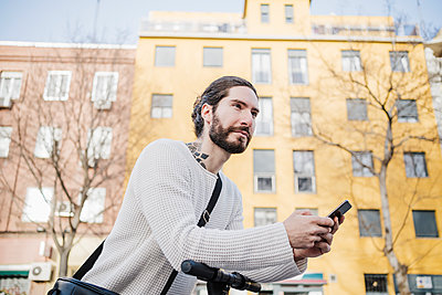 Hipster man with smart phone leaning on electric push scooter while looking away - p300m2274033 by Eva Blanco