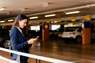 Female professional using smart phone while standing in parking lot - p300m2287380 by Francesco Morandini
