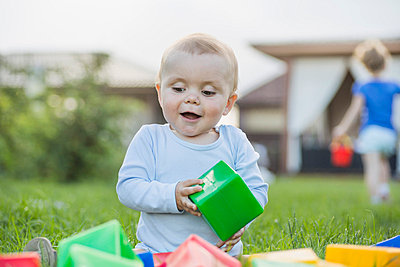 Happy baby in the garden playing with building blocks - p301m744245f by Vladimir Godnik