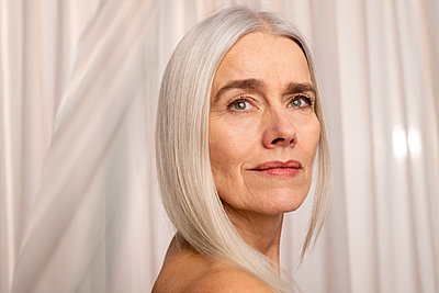 Portrait of elderly woman with long grey hair - p608m2157677 by Jens Nieth