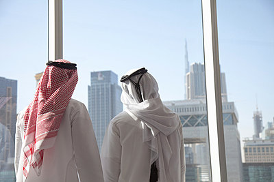 Middle eastern businessmen looking at dubai through office window - p9244776f by Image Source