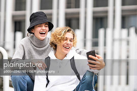 Young friends laughing while taking selfie on mobile phone - p300m2242765 by GER photography