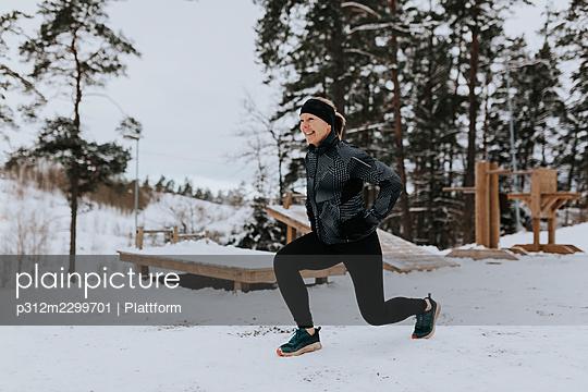 Smiling woman exercising at winter - p312m2299701 by Plattform