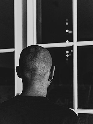Rear view, Bald man looking out of window - p1267m2258001 by Jörg Meier