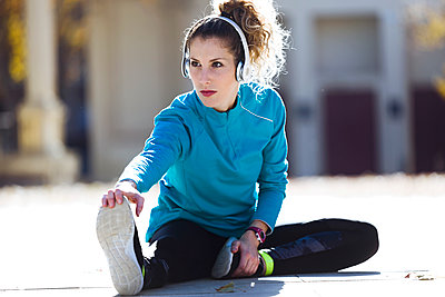 Young woman with headphones stretching - p300m1562811 by Josep Suria