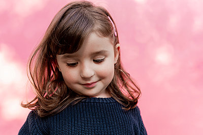Portrait of smiling little girl in front of  pink background - p300m2170183 by Gemma Ferrando