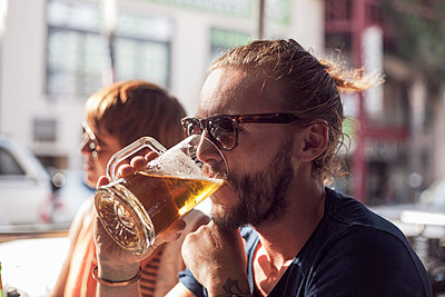 Mid adult man drinking beer while sitting in cafe - p300m2224974 by LOUIS CHRISTIAN