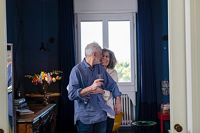 Smiling woman embracing man holding wineglass while standing at home - p300m2265919 by Emma Innocenti