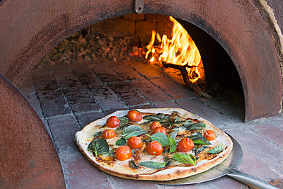 Fresh pizza on peel in traditional oven - p301m1070118f by Tobias Titz