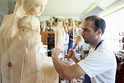 Sculptor chiseling figure from wood - p429m747169f by Stefano Gilera