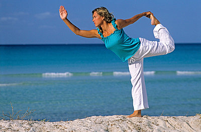 Woman doing yoga at the beach - p8850291 by Oliver Brenneisen