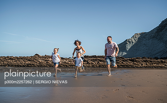 Playful family running at beach against blue sky - p300m2257262 by SERGIO NIEVAS