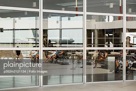 Airplane reflected in window at airport - p352m2121134 by Folio Images
