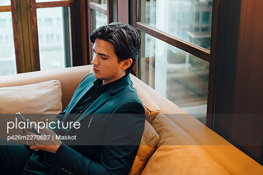 Male entrepreneur using smart phone while sitting on sofa at office - p426m2270627 by Maskot
