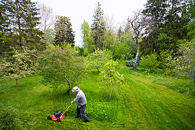 Man in hat mowing lawn - p1418m1572039 by Jan Håkan Dahlström
