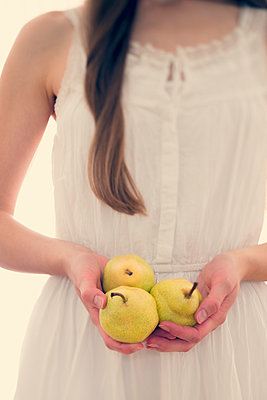 Young woman holding three pears in her hands, partial view - p300m949727f by Biederbick&Rumpf