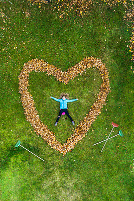 Woman lying in heart made out of fallen leaves - p312m2118544 by Johner